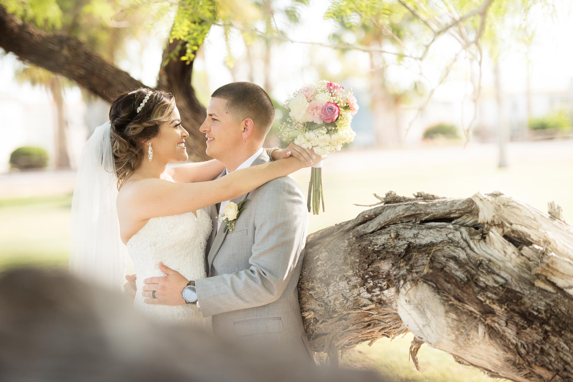 couple embrace rustic tree trunk wedding portrait session